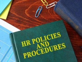 Book with title HR policies and procedures on a table.