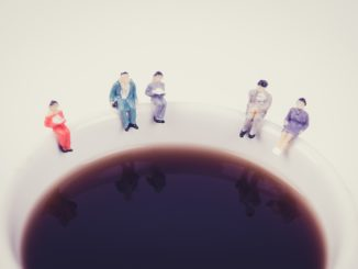 miniature people business team sitting on white coffee cup