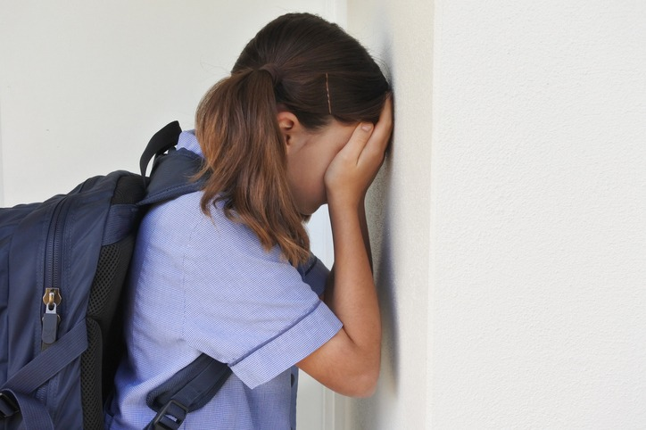 Sad young schoolgirl covering her face and crying against a wall