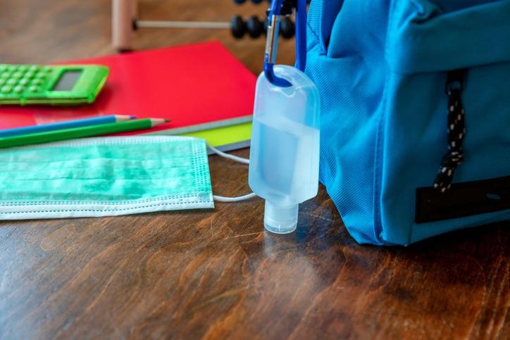 Sanitizer gel on a blue color school bag wooden background